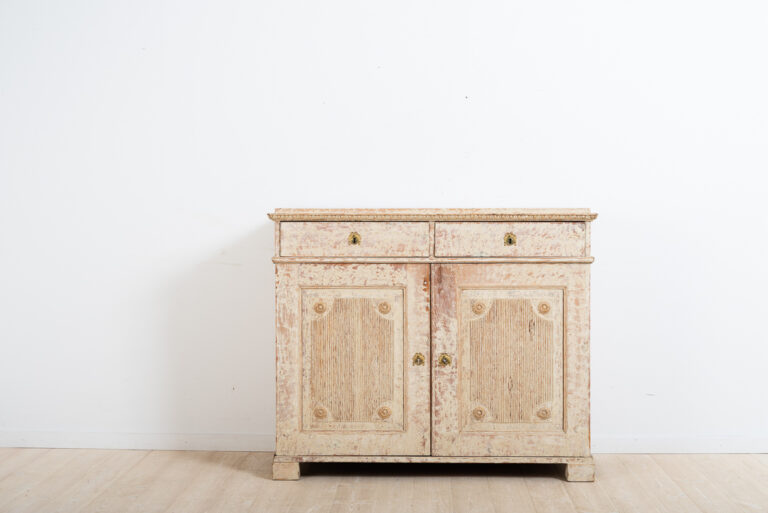 Two door gustavian sideboard with original paint. Decorated with fluted panels and carved wooden decorations. Dry scarped to the original paint