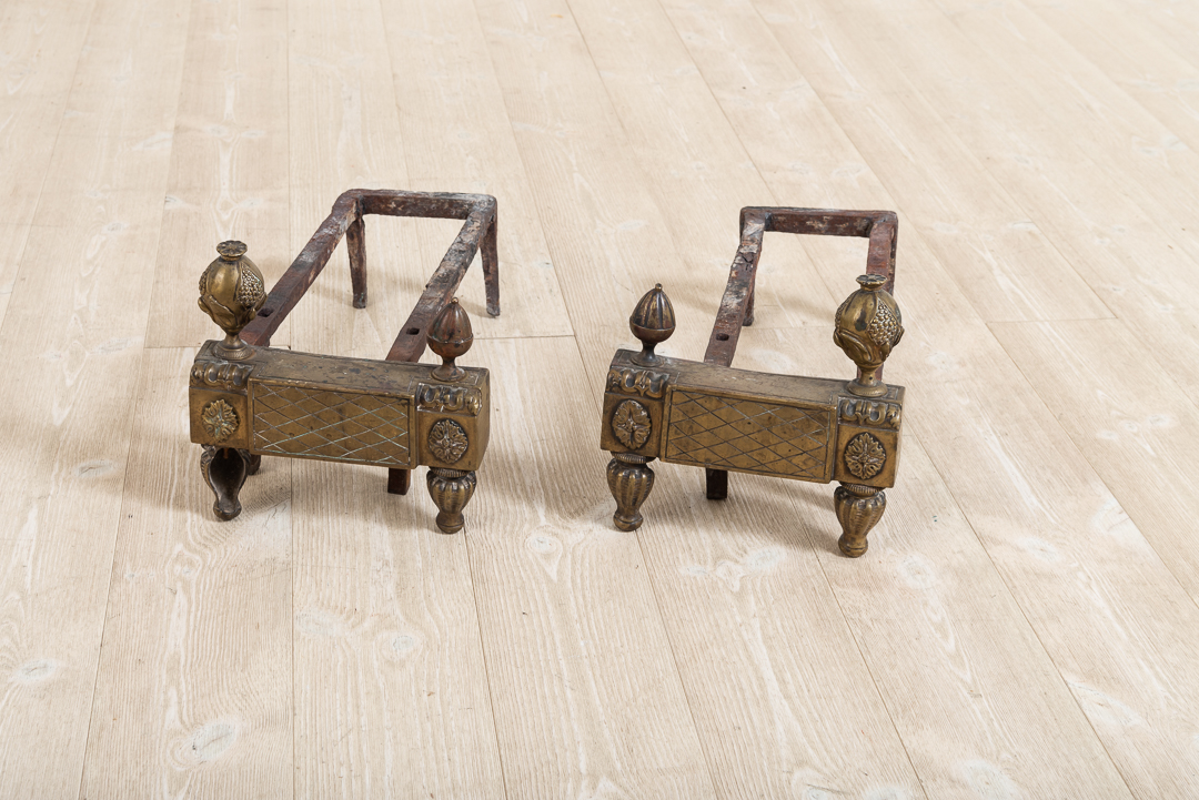 Pair of two andirons in iron. The frame is decorated with gustavian decorations in brass. Manufactured during the late 1700s.