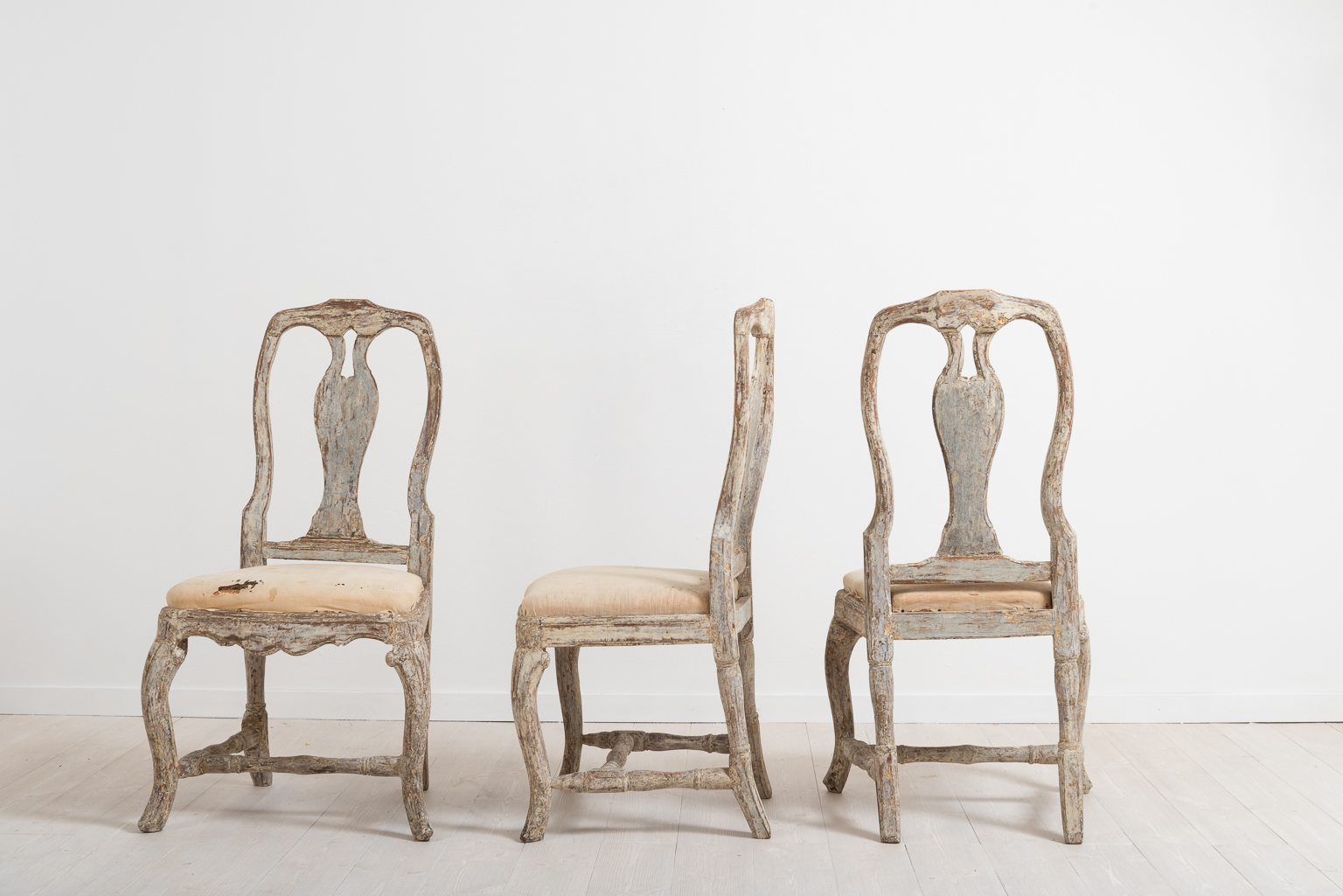 Three late baroque chairs from the middle of Sweden. Manufactured around 1770 the chairs are dry scarped to the original paint. Original seats