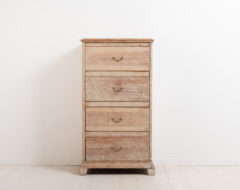 Chest of drawers in neoclassic style. The style shows in the straight shape and simple decor. The chest is unusually tall and narrow. Made in pine