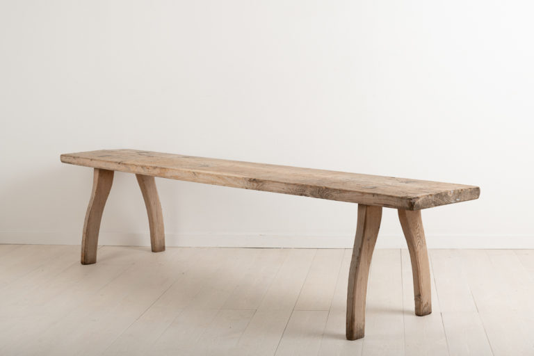 Primitive and rustic bench from northern Sweden. The bench is folk art and from the late 18th century. It has curved rococo legs and a natural patina after some 250 years of use.