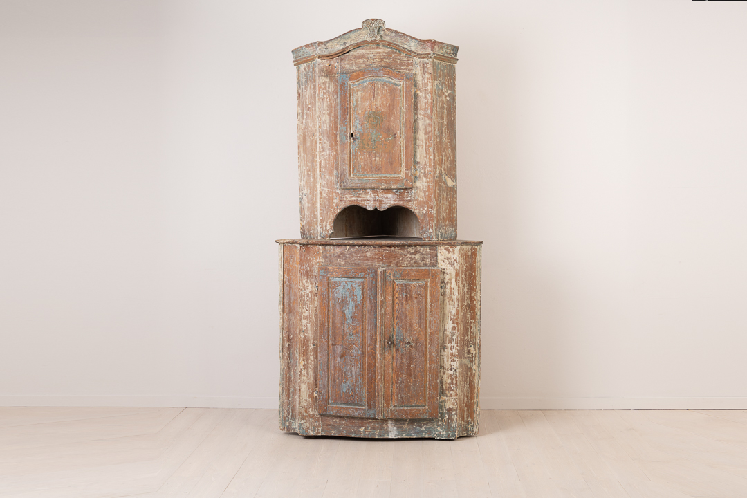 Rococo corner cabinet from around 1770. Made in Northern Sweden the cabinet is in two parts with rustic patina and original blue paint