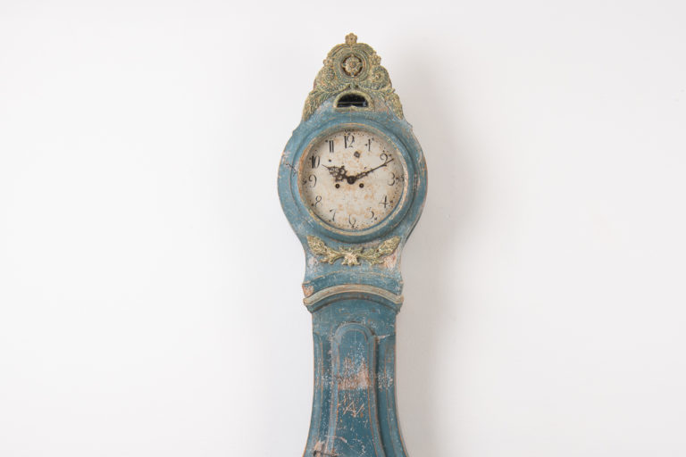 Blue long case clock from the transitional time between rococo and neoclassicism. Hand carved wooden decorations around the glass in the lid and hood