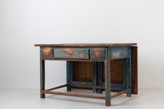 Folk art work table from northern Sweden. The table has three drawers in the rim and a drop leaf / extra table top. Made around 1810 to 1820 in painted pine