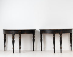Black demi lune tables from Sweden. The tables are an original pair and two halves of one whole. They would for example work well as console tables.