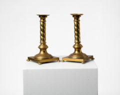 Swedish candle sticks in brass made during the later part of the 1800s. The pair are of the gustavian style with a square base, small round feet and a turned column