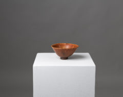 Stoneware bowl by Carl-Harry Stålhane with hare's fur glaze. The bowl is glazed with muted but fiery shades of yellow, orange and brown