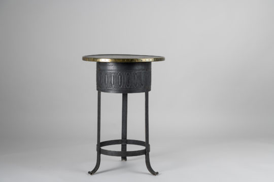 Swedish Art Deco table from the early 20th century, around 1920 to 1930. The table has a frame in metal with a patterned surface and a brass rim around the table top