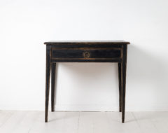 Black gustavian and neoclassic table from the early 1800s. The table is Swedish and has straight tapered legs and a large centred drawer.