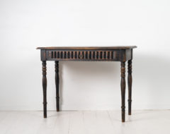 Black Swedish antique desk from the late 1800s, around 1860 to 1870. The desk is pine with a large drawer with unusual decor.